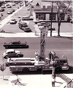 Black and white photo of a fire truck with the ladder extended